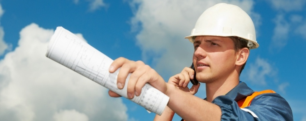 builder worker in uniform with blueprint project outdoors